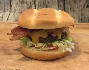 A burger with bacon, lettuce, tomato, and pickles.