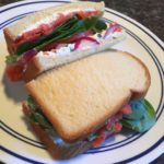 Salmon lox sandwich with capers, spinach, tomato, and onion.