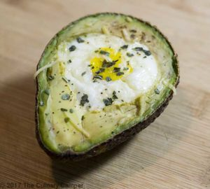 Healthy avocado egg breakfast topped with parmesan cheese and herbs.