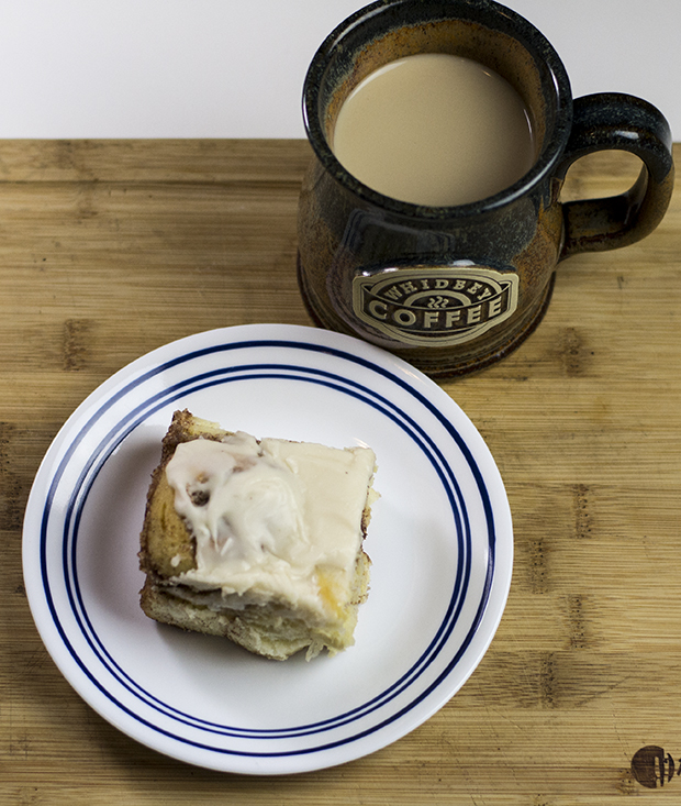 A hot cup of coffee with a gooey cinnamon roll.
