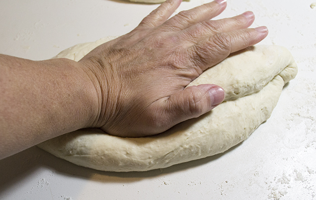 Pressing baguette dough after the fold.
