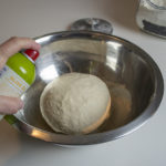 Spray pizza dough with non stick olive oil before letting it rise.