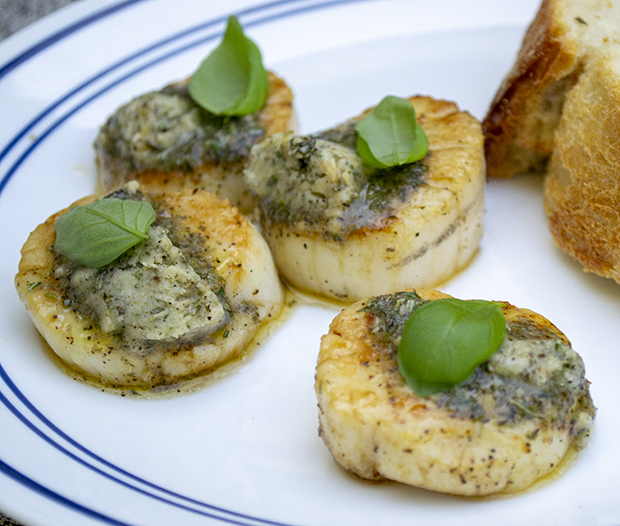 Scallops seared on a salt block and served with a compound butter and garlic bread.